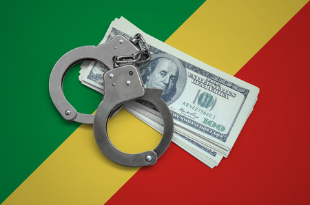 Congo flag  with handcuffs and a bundle of dollars. Currency corruption in the country. Financial crimes.