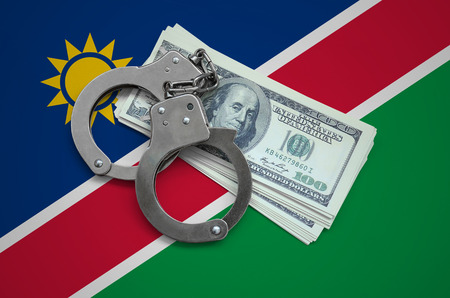 Namibia flag  with handcuffs and a bundle of dollars. Currency corruption in the country. Financial crimes.