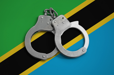 Tanzania flag and police handcuffs. The concept of observance of the law in the country and protection from crime.
