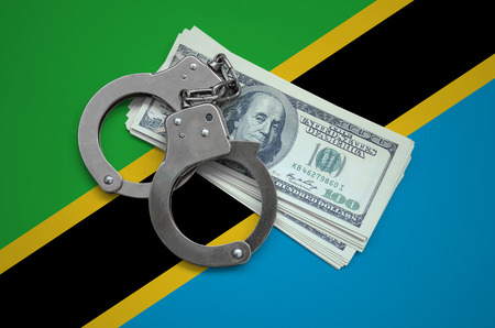 Tanzania flag  with handcuffs and a bundle of dollars. Currency corruption in the country. Financial crimes. 版權商用圖片