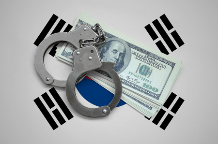 South Korea flag  with handcuffs and a bundle of dollars. Currency corruption in the country. Financial crimes. 版權商用圖片