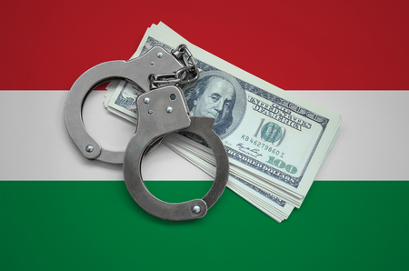 Hungary flag  with handcuffs and a bundle of dollars. Currency corruption in the country. Financial crimes.