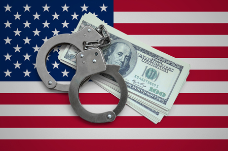 United States of America flag  with handcuffs and a bundle of dollars. Currency corruption in the country. Financial crimes. 版權商用圖片