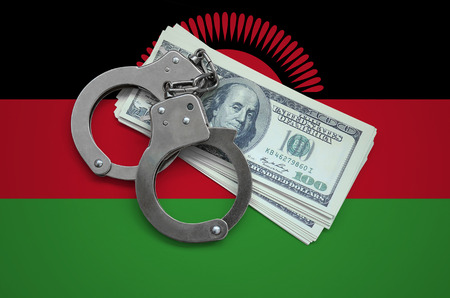 Malawi flag  with handcuffs and a bundle of dollars. Currency corruption in the country. Financial crimes.