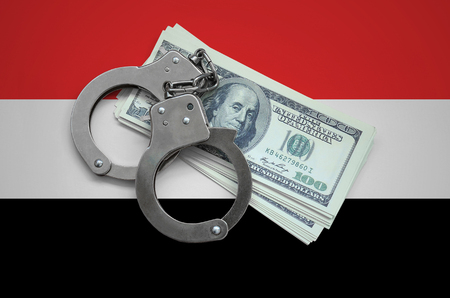 Yemen flag  with handcuffs and a bundle of dollars. Currency corruption in the country. Financial crimes.