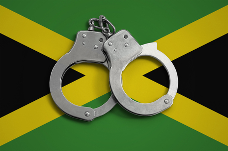 Jamaica flag  and police handcuffs. The concept of observance of the law in the country and protection from crime. Stock Photo
