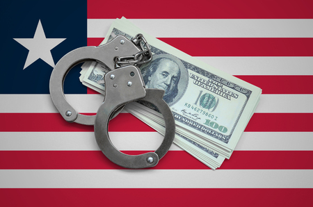 Liberia flag  with handcuffs and a bundle of dollars. Currency corruption in the country. Financial crimes. Stock Photo