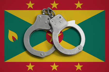Grenada flag  and police handcuffs. The concept of observance of the law in the country and protection from crime.