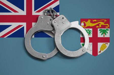 Fiji flag  and police handcuffs. The concept of observance of the law in the country and protection from crime.