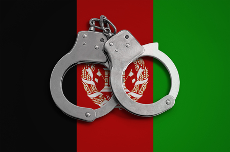 Afghanistan flag and police handcuffs. The concept of observance of the law in the country and protection from crime.