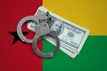 Guinea Bissau flag  with handcuffs and a bundle of dollars. Currency corruption in the country. Financial crimes.