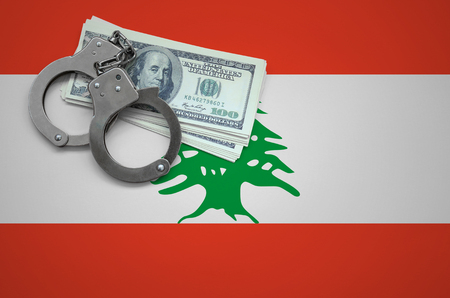 Lebanon flag  with handcuffs and a bundle of dollars. The concept of breaking the law and thieves crimes. Imagens