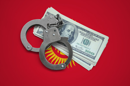 Kyrgyzstan flag  with handcuffs and a bundle of dollars. Currency corruption in the country. Financial crimes. 版權商用圖片