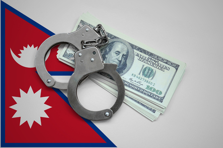 Nepal flag  with handcuffs and a bundle of dollars. Currency corruption in the country. Financial crimes. 版權商用圖片