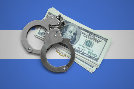 Nicaragua flag  with handcuffs and a bundle of dollars. Currency corruption in the country. Financial crimes.
