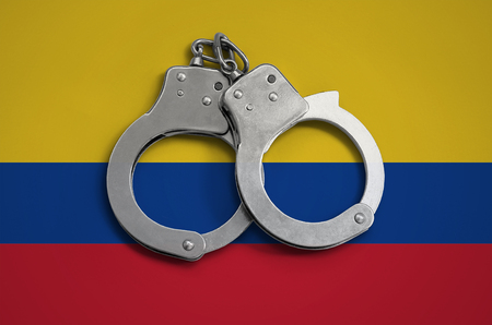 Colombia flag  and police handcuffs. The concept of observance of the law in the country and protection from crime. Stock Photo