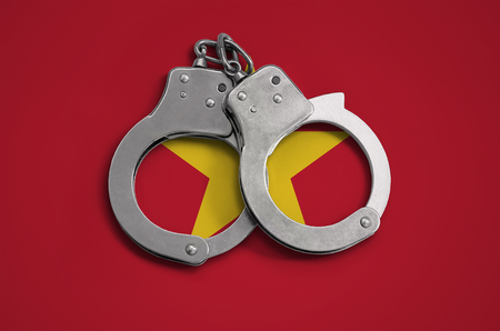 Vietnam flag  and police handcuffs. The concept of observance of the law in the country and protection from crime.