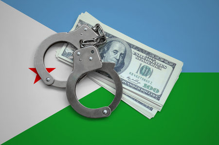 Djibouti flag  with handcuffs and a bundle of dollars. Currency corruption in the country. Financial crimes.