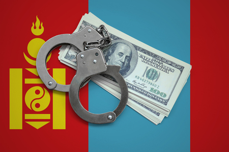 Mongolia flag  with handcuffs and a bundle of dollars. Currency corruption in the country. Financial crimes.