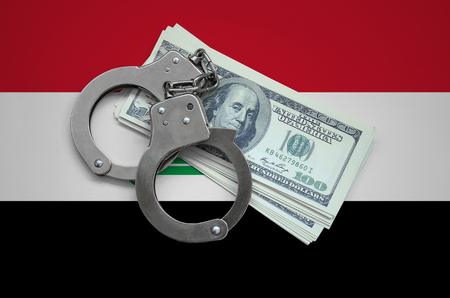 Iraq flag  with handcuffs and a bundle of dollars. Currency corruption in the country. Financial crimes.