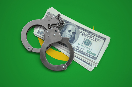 Mauritania flag  with handcuffs and a bundle of dollars. Currency corruption in the country. Financial crimes.