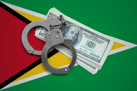 Guyana flag  with handcuffs and a bundle of dollars. Currency corruption in the country. Financial crimes.