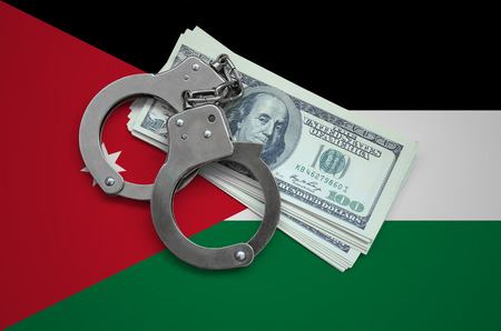 Jordan flag  with handcuffs and a bundle of dollars. Currency corruption in the country. Financial crimes.