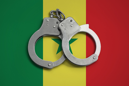 Senegal flag  and police handcuffs. The concept of observance of the law in the country and protection from crime.