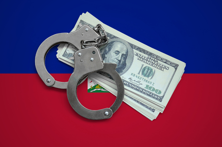 Haiti flag  with handcuffs and a bundle of dollars. Currency corruption in the country. Financial crimes.