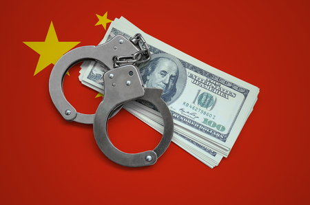 China flag  with handcuffs and a bundle of dollars. Currency corruption in the country. Financial crimes. 版權商用圖片