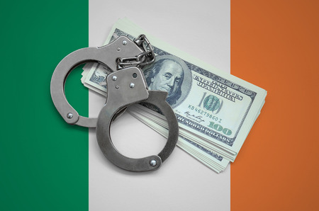 Ireland flag  with handcuffs and a bundle of dollars. Currency corruption in the country. Financial crimes.