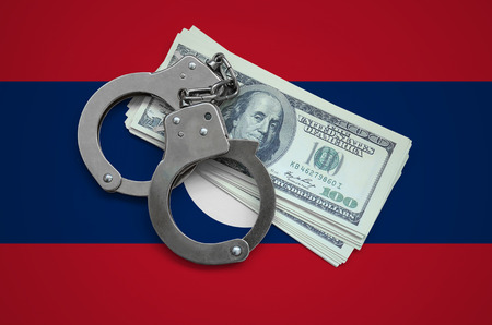 Laos flag  with handcuffs and a bundle of dollars. Currency corruption in the country. Financial crimes. 版權商用圖片