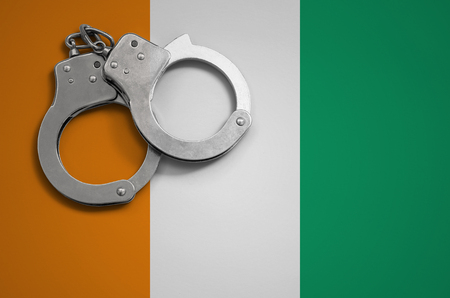 Ivory Coast flag  and police handcuffs. The concept of crime and offenses in the country. Reklamní fotografie