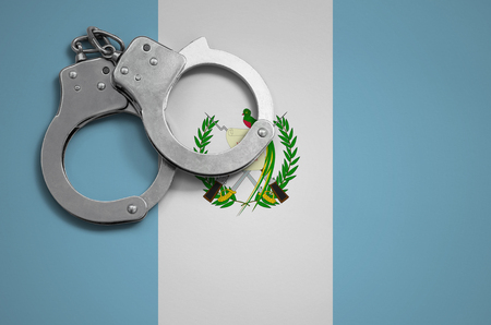 Guatemala flag  and police handcuffs. The concept of crime and offenses in the country.