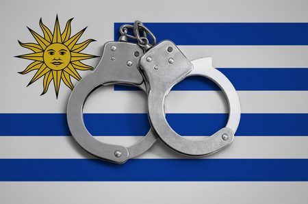Uruguay flag  and police handcuffs. The concept of observance of the law in the country and protection from crime.