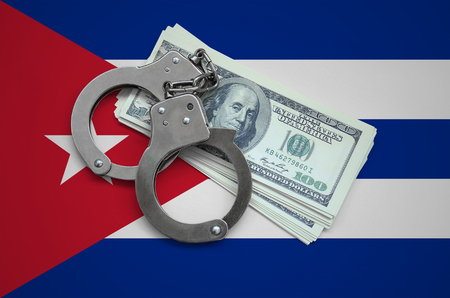 Cuba flag  with handcuffs and a bundle of dollars. Currency corruption in the country. Financial crimes.