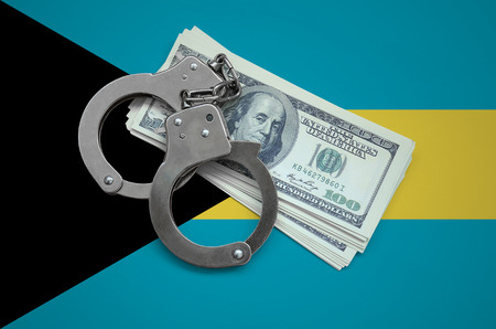 Bahamas flag  with handcuffs and a bundle of dollars. Currency corruption in the country. Financial crimes.