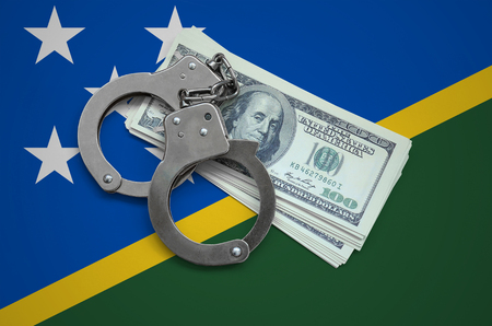 Solomon Islands flag  with handcuffs and a bundle of dollars. Currency corruption in the country. Financial crimes. 版權商用圖片