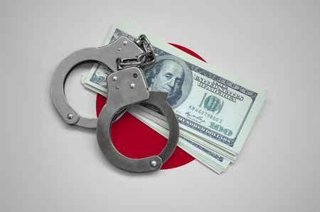 Japan flag  with handcuffs and a bundle of dollars. Currency corruption in the country. Financial crimes.