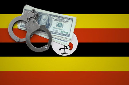 Uganda flag  with handcuffs and a bundle of dollars. The concept of breaking the law and thieves crimes.