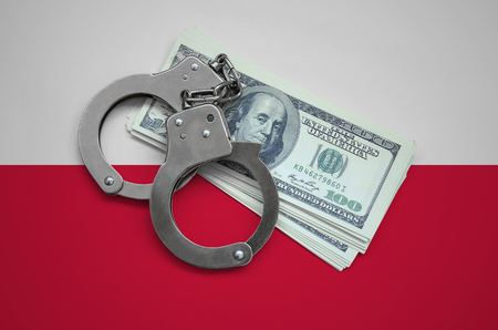 Poland flag  with handcuffs and a bundle of dollars. Currency corruption in the country. Financial crimes. 版權商用圖片 - 105014614