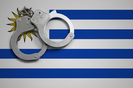 Uruguay flag  and police handcuffs. The concept of crime and offenses in the country. Stock Photo