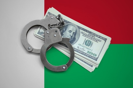 Madagascar flag  with handcuffs and a bundle of dollars. Currency corruption in the country. Financial crimes.