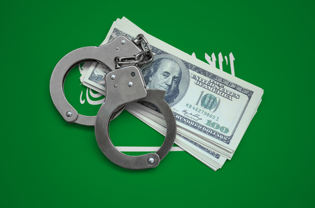 Saudi Arabia flag  with handcuffs and a bundle of dollars. Currency corruption in the country. Financial crimes. 版權商用圖片