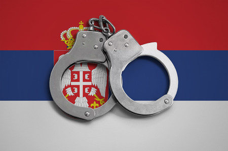 Serbia flag  and police handcuffs. The concept of observance of the law in the country and protection from crime.