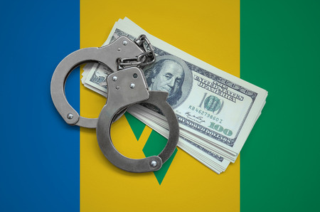 Saint Vincent and the Grenadines flag  with handcuffs and a bundle of dollars. Currency corruption in the country. Financial crimes.