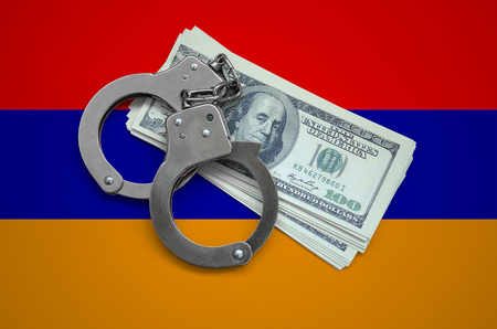 Armenia flag  with handcuffs and a bundle of dollars. Currency corruption in the country. Financial crimes.