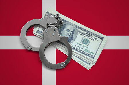 Denmark flag  with handcuffs and a bundle of dollars. Currency corruption in the country. Financial crimes. 版權商用圖片
