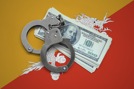 Bhutan flag  with handcuffs and a bundle of dollars. Currency corruption in the country. Financial crimes. 版權商用圖片