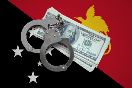 Papua New Guinea flag  with handcuffs and a bundle of dollars. Currency corruption in the country. Financial crimes. 版權商用圖片